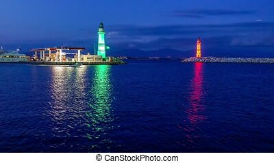 Entrance to yacht marina with green and red lighthouses by...