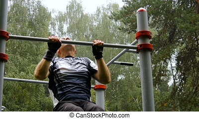 A man is doing chin-ups. In the park, outdoors.