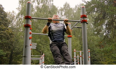 A man is doing chin-ups. In the park, outdoors 4K
