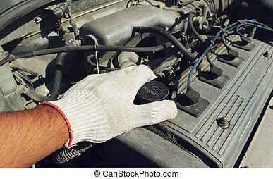 The cover oil filler neck of the car in a hand
