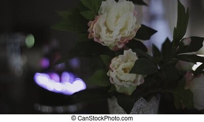 View at white flowers in bouquet stand in white vase. Evening lights. Leaf
