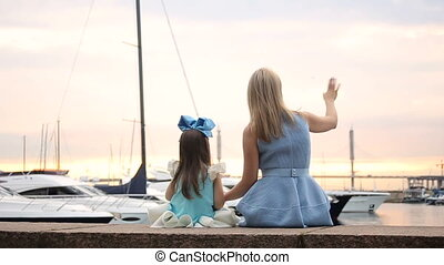 mother sitting with baby daughter three years and waving to the ships