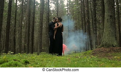 man and a woman in black robes standing in the woods