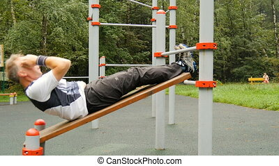 A man is exercising at an open pitch. It makes abdominal...