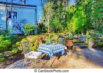 Backyard patio area with table set and nice landscaping...