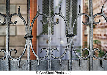 Wrought Iron - Wrought iron fence fragment in front of a...
