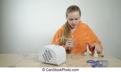 Teenage girl preparing to use a nebulizer for asthma...