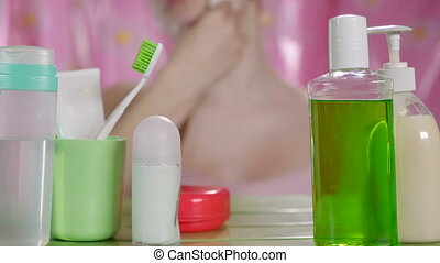 Young girl cleaning face skin with soft cotton pad in bathroom