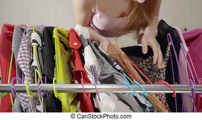 Frustrated teenage girl in front of clothing rack choosing...