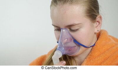 Teenage girl using nebulizer with breathing mask at home...