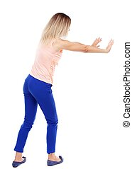 back view of woman pushes wall. Isolated over white...
