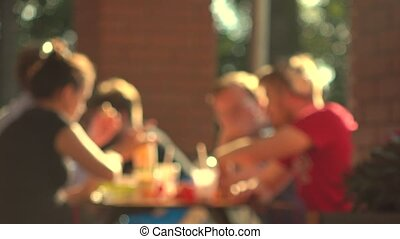Blurred young people eating fast food outdoor. 4K background...