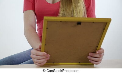 Teenage girl looking at the framed photo print in her hands...