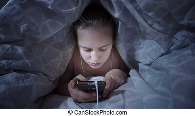 Teenage girl lying down in the bed covered with blanket using mobile phone at night