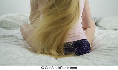 Blonde long haired girl combing her long hair sitting on bed...