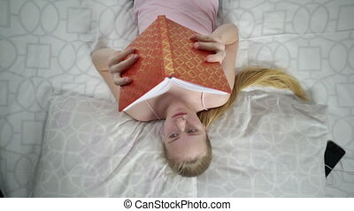 Yawning teenage girl while reading a book fell asleep on the...