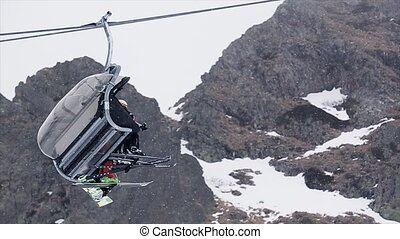 Ski lift with people ride up at snowy mountains. Ski resort. Snow falls. Snowboarding. Open cabin