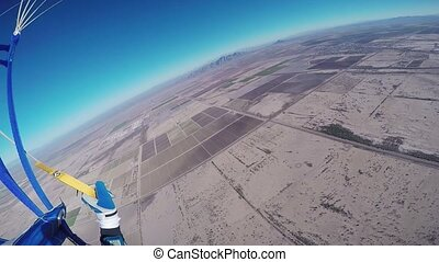 Professional skydiver parachuting in blue sky above Arizona. Sunny. Landscape