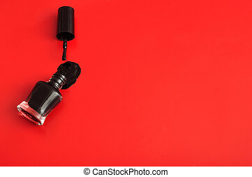 An open bottle of black nail polish displayed with its brush on a red background