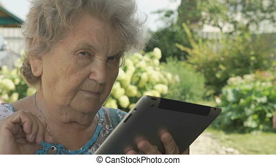 Elderly woman holding a digital tablet outdoors