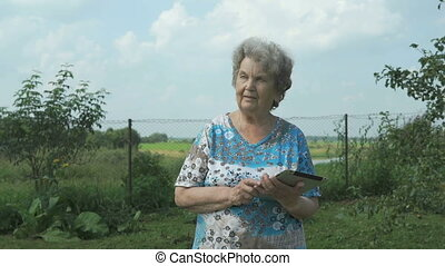 Aged woman 80s holding a digital tablet outdoors