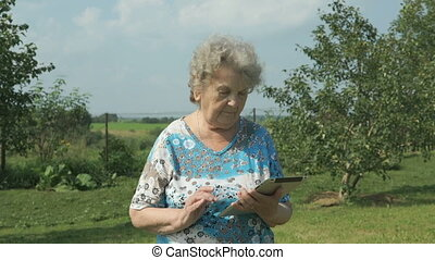 Ederly woman holding a digital tablet outdoors