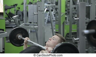 The man raises the bar in the gym
