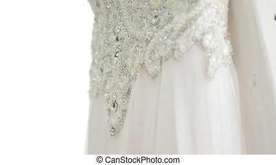 A closeup of white wedding dress decorated with embroidered crystals