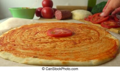 Woman placing tomato slices over pizza. Cooking, part of the...