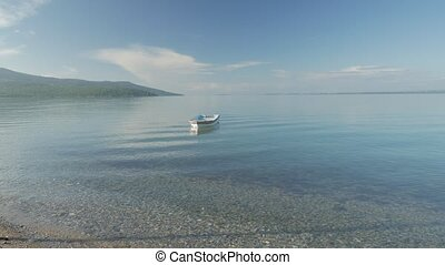 Lonely row boat floating on clear water with small waves in...