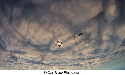 Skydiver opens parachute in clouds, flight. Extreme sport. Evening. Dangerous.