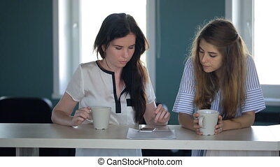 Females are looking in cellphone in time of coffee break....