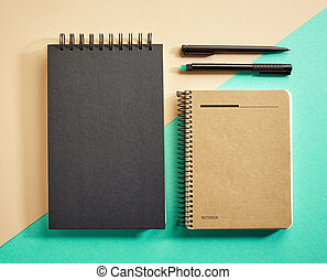 top view of notebooks and pens on colorful paper background