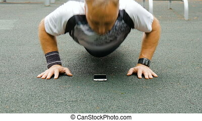 A man is exercising at an open pitch - Doing exercises with...