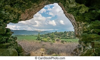 Zoom view from ruins of ancient Myus tunnel looks out to spectacular valley and cloudscape in Caria, Turkey. Time lapse 4K.