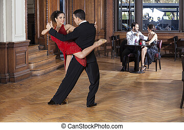 Tango Dancers Performing Piernazo While Mid Adult Couple...