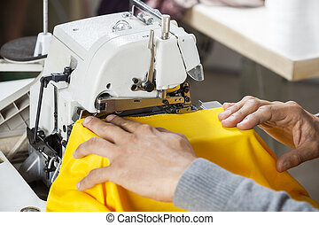 Tailor Sewing Fabric At Workbench - Cropped image of tailor...