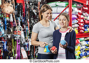 Girl Buying Toys With Mother In Pet Store - Portrait of...