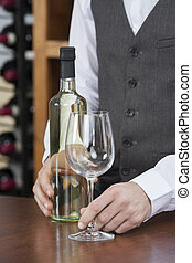 Bartender With White Wine And Glass At Counter - Midsection...