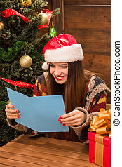 Beautiful girl reading New Year and Christmas congratulation