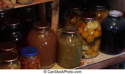 Food in jars. Jars on wooden shelves. Plums and apricots....