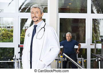 Confident Mature Doctor Smiling At Rehab Center