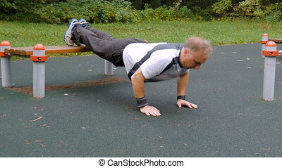 A man is exercising at an open pitch. Early in the morning,...
