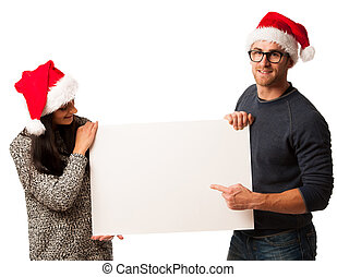 Young couple in santa hats holding blank board for advertisement.