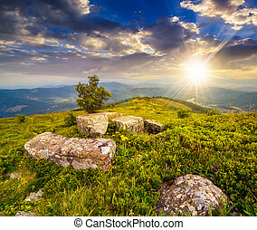 boulders on hillside meadow in mountain at sunset - small...