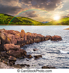 mountain lake with rocky shore at sunset