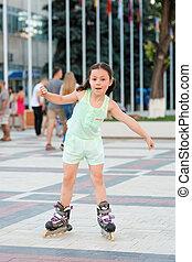 Little pretty girl on roller skates at a park - Little...
