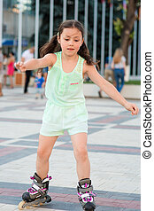 Little pretty girl on roller skates at a park - Little...