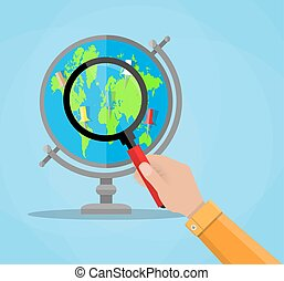 Globe with continents and magnifying glass