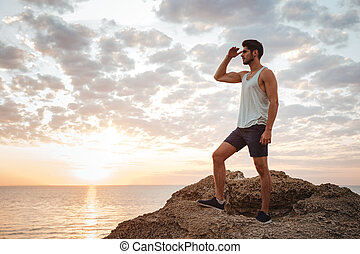 Young casual man standing on the mountain rock by the sea...